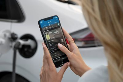A woman checking her Hyundai IONIQ's status on her phone while charging the car.